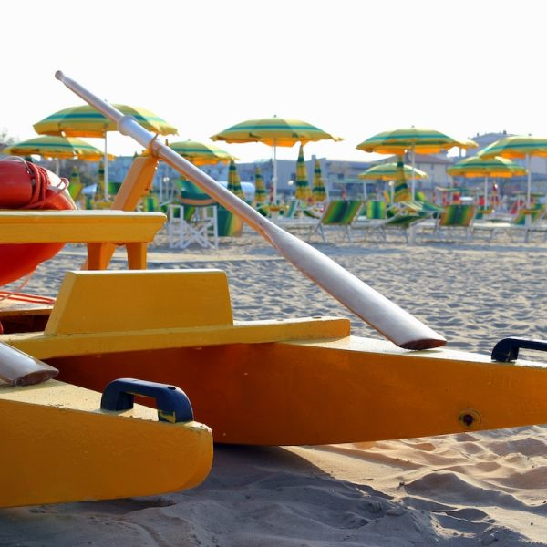Travel to Rimini, Italy. The catamaran on the foreground on the empty beach with a lot of sunbeds and umbrellas on the background.